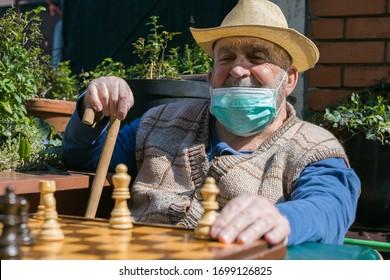 elderly man playing chess on terrace during coronavirus epidemic quarantine