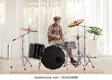 Elderly man playing drums inside a house