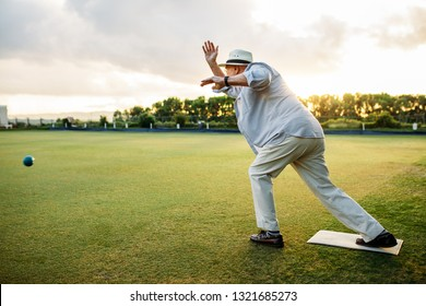Elderly man playing a game of boules. Old man in hat throws a boules standing in position in a lawn.