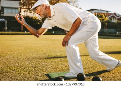 Elderly man playing a game of boules. Senior man in hat throws a boules standing in position in a lawn.