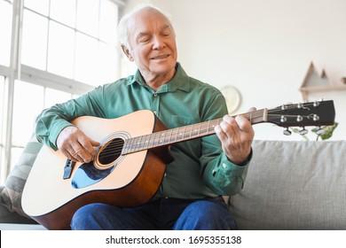 Elderly man playing guitar at home