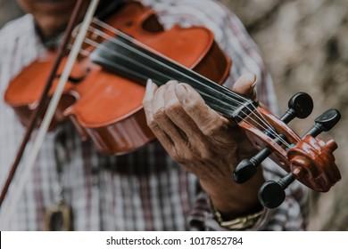 An elderly man playing a violin.