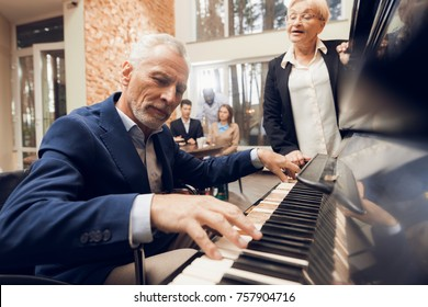 An elderly man plays the piano in a nursing home. He is listened to by an elderly woman and a company of young people with a doctor at the back.