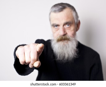 An elderly man pointing with his finger