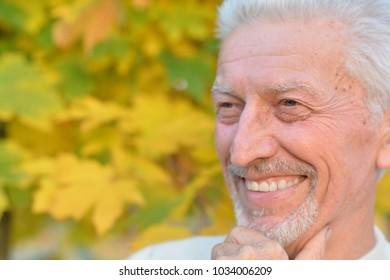 elderly man posing  in autumn park