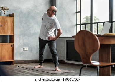 Elderly man practicing yoga or fitness during trikonasana. Positive mood on sports, stay at home.