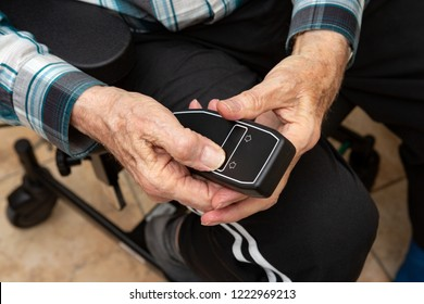 An elderly man pusching a black remote control of a electric weelchair while taking occupational therapy
