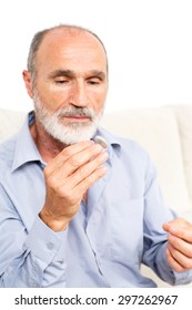 Elderly man putting some hearing aid in his ear
