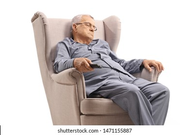 Elderly man in pyjamas sleeping in an armchair and holding a remote control isolated on white background