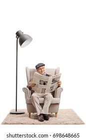 Elderly man reading a newspaper in an armchair next to a lamp isolated on white background