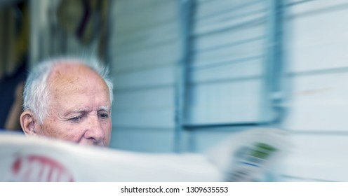 Elderly man reading newspaper, front view.