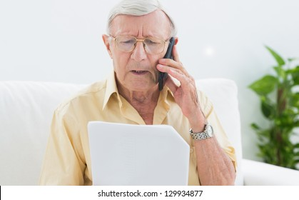 Elderly man reading papers on the phone