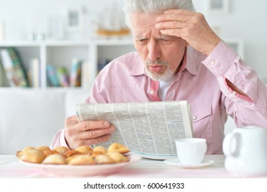 Elderly man reads a newspaper