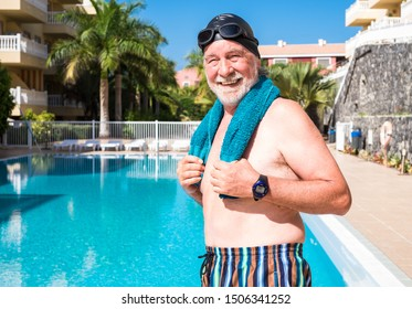 An elderly man ready to play sports and swim in the blue pool. Man with white beard and mustache with swimming cap and goggles. A healthy lifestyle under the sun.
