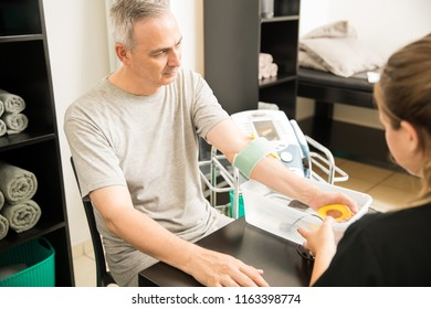 Elderly man receiving electrotherapy from therapist in hospital