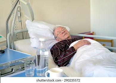 Elderly man recuperating in a hospital lying asleep in a bed on the ward in his pyjamas still wearing his spectacles in health care and medical concept