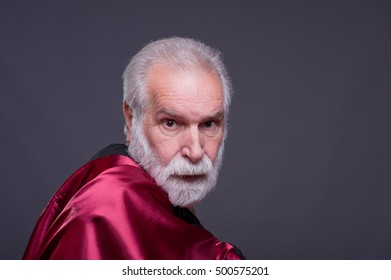 Elderly man with red costumes, serious expression.