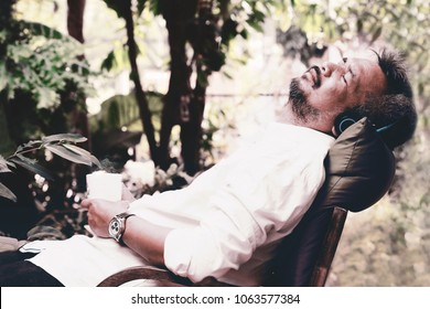 Elderly man relax in the garden,man laying on chair with pillow holding hot coffee cup and enjoy the music from headset.He looks relax and peaceful.Concept of relax after work or early retirement.