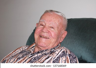 Elderly man relaxing and smiling.