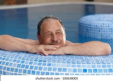 Elderly man relaxing in spa, smiling, looking away.