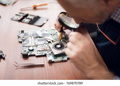 An elderly man is repairing a computer. He is in a repair shop. He uses different tools. He is a repair specialist.