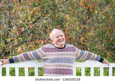 elderly man resting on white wooden bench in autumn park