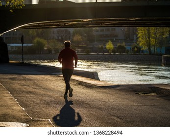 Elderly man running along the river early in the morning