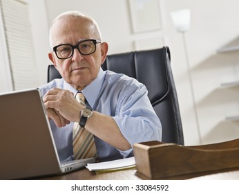 An elderly man is seated at a desk in front of a laptop and is looking at the camera.  Horizontally framed shot.