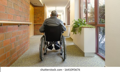 An elderly man, senior, is sitting in a wheelchair in the corridor near the window with his back to the camera. Nursing home.