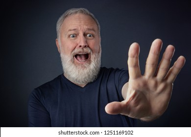 Elderly man in shirt and scared with his stretched hand forward for stopping something
