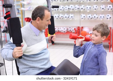 elderly man in shop on  sports exerciser and boy with barbell in hand, focus on senior