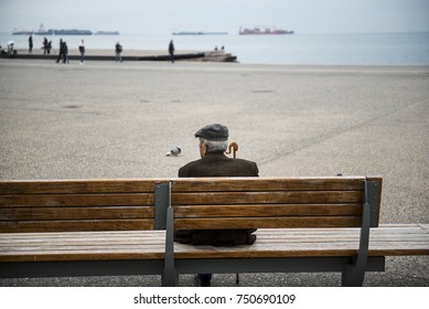 An elderly man sits on a bench as he watches the view at the seafront of the northern Greek city of Thessaloniki.