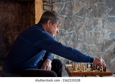 Elderly man sits on chair in country house and plays chess with himself. Waiting and loneliness. Profile view