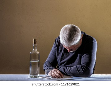 an elderly man sits at a table with a bottle of alcohol