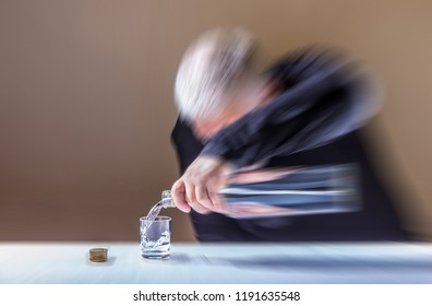 An elderly man sits at a table and pours alcohol into a glass