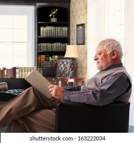 Elderly man sitting in armchair reading book at study at home.