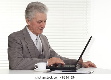 an elderly man sitting at the computer on a isolate