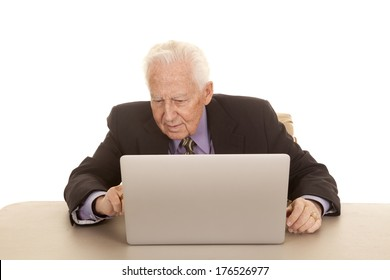 An elderly man sitting at a computer in a suit and tie.