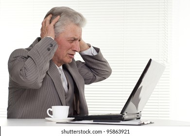 an elderly man sitting at the laptop on a white background