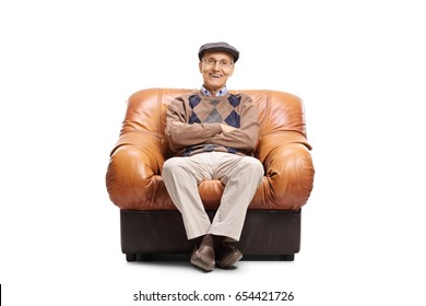 Elderly man sitting in a leather armchair and looking at the camera isolated on white background