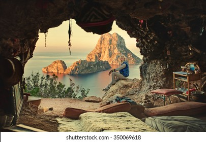 An elderly man sitting next to hippies cave overlooking the rock and the sea