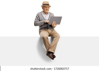 Elderly man sitting on a blank panel and using a laptop computer isolated on white background