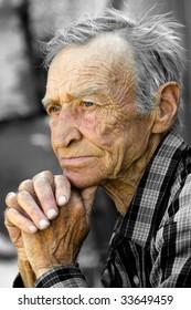 Elderly the man, sitting in thoughtfulness