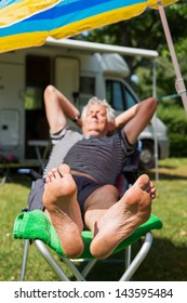 Elderly man is sleeping at the camping with bare feet (focus on feet)