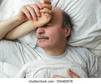 The elderly man sleeps, holding the hand of his beloved. Good family relationships in old age