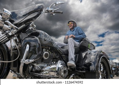 Elderly man smiles as he sits on the back of a powerful three-wheel motorcycle on a stormy day with dark clouds, nearby trees, clouds and homes reflected in the black shining surface of the cycle