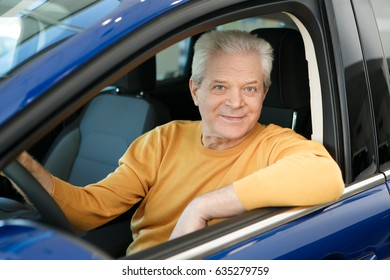 Elderly man smiling happily sitting in his car comfort luxury travelling safety insurance pensioner retired retiring seniority lifestyle transportation automotive sales offer driving driver owning