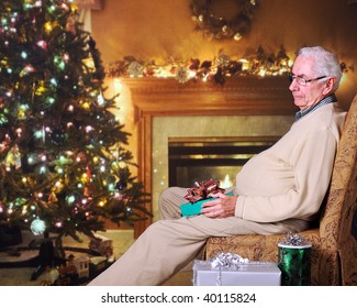 An elderly man snoozing with a wrapped gift on his lap in a festively decorated living room.