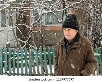 Elderly man standing near the wooden fence of rural house during a snowfall. Cold weather, snow winter