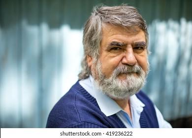 elderly man standing outside on blue wooden background